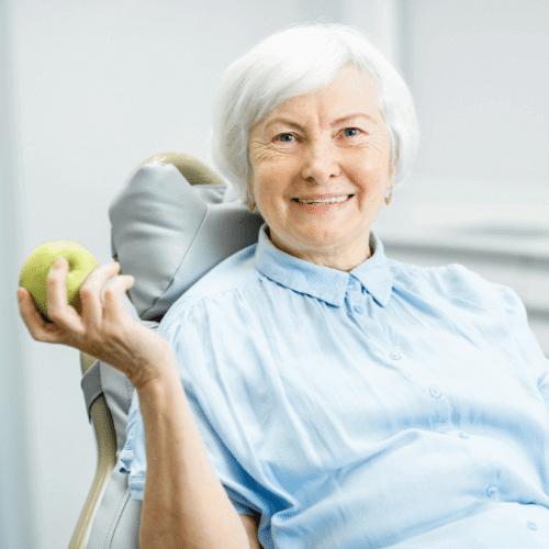 Ältere Frau mit Zahnprothese hält Apfel in der Hand